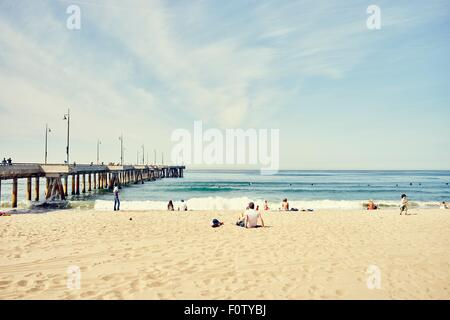 People relaxing next to pier, Venice Beach, Los Angeles, California - Stock Photo
