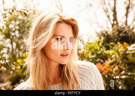 Beautiful mid adult woman with long blond hair in garden - Stock Photo