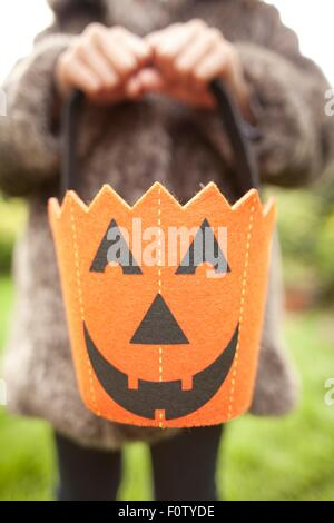 Girl holding up halloween pumpkin bag for trick or treating - Stock Photo