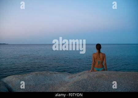 Young woman sitting on rock, looking out to sea, Costa rei, Sardinia, Italy - Stock Photo