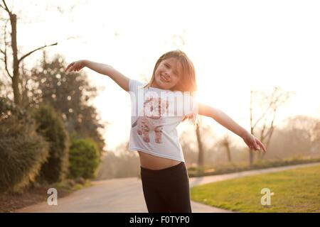 Portrait of young girl in park, smiling - Stock Photo