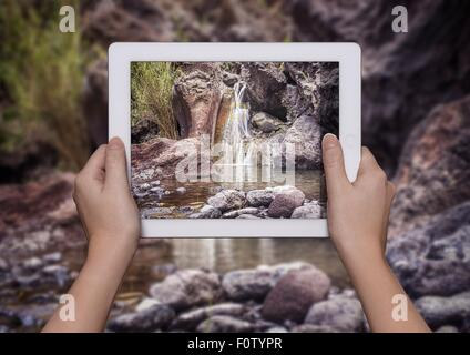 Hands of young woman holding up digital tablet with view of Samaria Gorge in front of view of Samaria Gorge, Crete, - Stock Photo