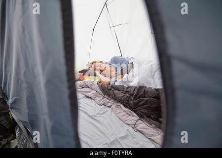 Mother lying in tent with toddler son using digital tablet - Stock Photo