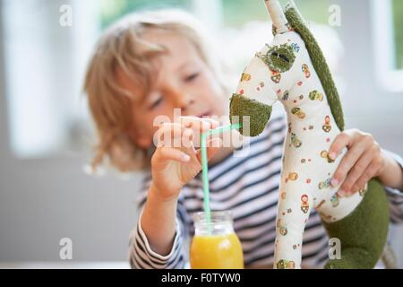 Young boy pretending to feed drink to soft toy - Stock Photo
