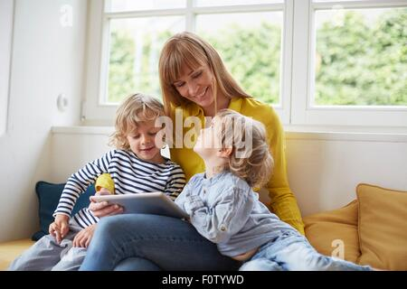 Mother and two sons, sitting in window seat, looking at digital tablet - Stock Photo