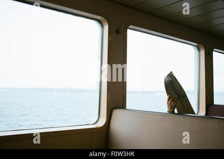 Mans hand holding up newspaper on seat on passenger ferry - Stock Photo