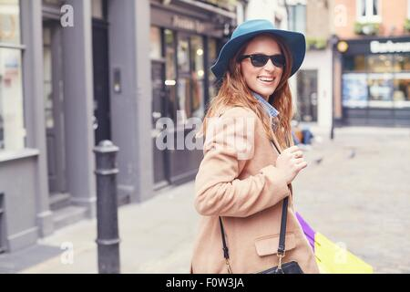 Portrait of stylish young woman looking over her shoulder, London, UK - Stock Photo