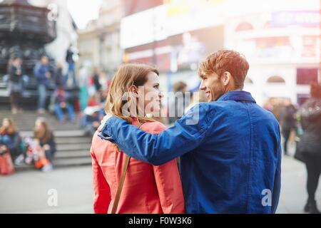Tourist couple strolling at Piccadilly Circus, London, UK - Stock Photo