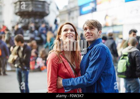Tourist couple looking up from Piccadilly Circus, London, UK - Stock Photo