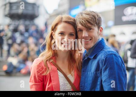 Portrait of tourist couple at Piccadilly Circus, London, UK - Stock Photo