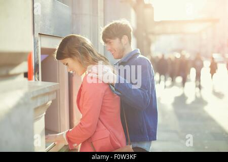 Couple withdrawing money from cash machine on street, London, UK - Stock Photo
