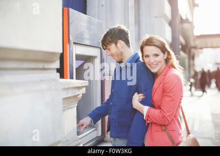 Couple withdrawing money from street cash machine, London, UK - Stock Photo