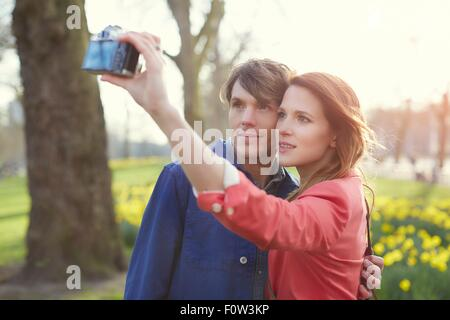 Couple taking camera selfie in park, London, UK - Stock Photo