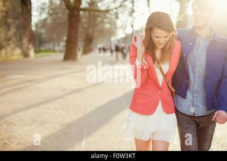 Romantic couple strolling in sunlit park, London, UK - Stock Photo