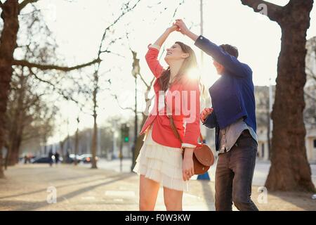 Romantic couple twirling in sunlit park, London, UK - Stock Photo