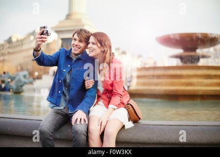 Couple taking camera selfie at Trafalgar Square fountain, London, UK - Stock Photo