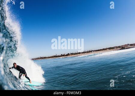 Close up of ocean wave and mid adult man surfing, Carlsbad, California, USA - Stock Photo