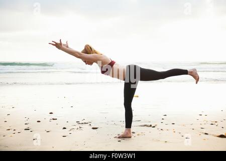 Mid adult woman practicing warrior yoga pose on beach - Stock Photo