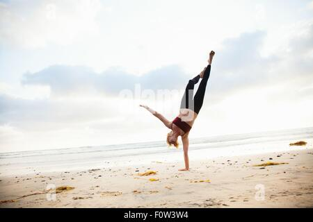 Mid adult woman practicing yoga position on beach - Stock Photo
