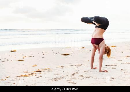 Mid adult woman upside down in yoga position on beach - Stock Photo