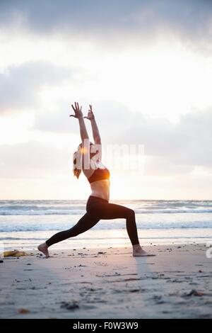 Mid adult woman practicing warrior yoga pose on beach at sunset - Stock Photo