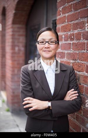 Businesswoman with arms crossed next to brick wall - Stock Photo
