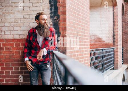 Man with beard leaning on balcony looking away - Stock Photo