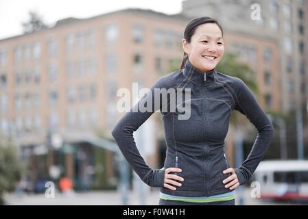 Female runner taking break in city centre, San Francisco, California - Stock Photo