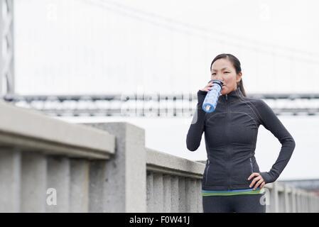 Female runner drinking on bridge, San Francisco, California - Stock Photo