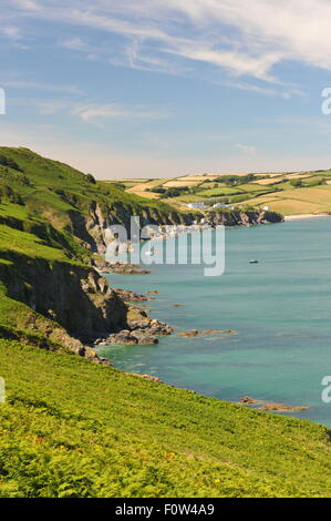 Sunny English coastline, calm sea with high wispy clouds and green fields.  Distant sailboat and coastal village. - Stock Photo