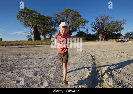 Boy playing on gravel road, Nxai Pan National Park, Kalahari Desert, Africa - Stock Photo