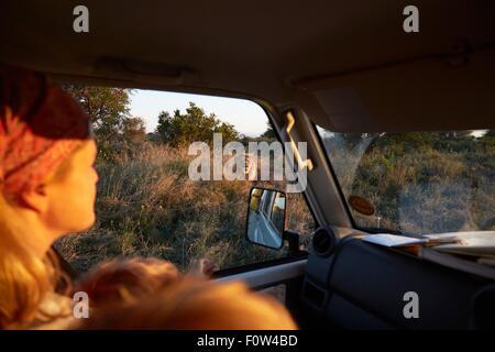 Woman travelling in vehicle, Nxai Pan National Park at sunset, Kalahari Desert, Africa - Stock Photo