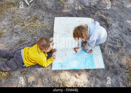 Boys reading map on gravel road - Stock Photo
