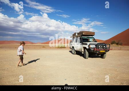 Boy walking to vehicle, Namib Naukluft National Park, Namib Desert, Sossusvlei, Dead Vlei, Africa - Stock Photo