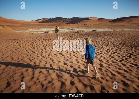 Boy walking in desert, Namib Naukluft National Park, Namib Desert, Sossusvlei, Dead Vlei, Africa - Stock Photo