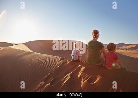Mother and sons sitting on sand dune, Namib Naukluft National Park, Namib Desert, Sossusvlei, Dead Vlei, Africa - Stock Photo