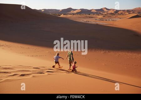 Mother and sons walking on sand dune, Namib Naukluft National Park, Namib Desert, Sossusvlei, Dead Vlei, Africa - Stock Photo