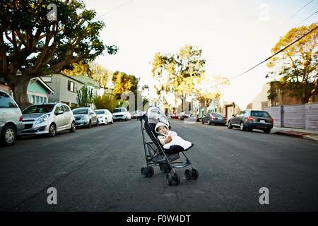 Baby boy in carriage on middle of road - Stock Photo