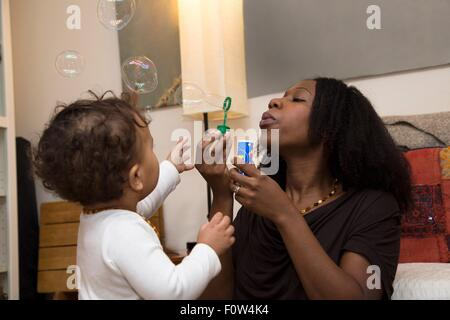 Mid adult woman and toddler daughter blowing bubbles - Stock Photo