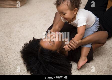 Mid adult woman playing with toddler daughter on rug - Stock Photo