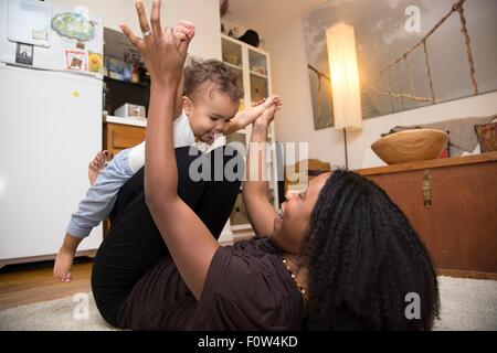 Mid adult woman lying on rug playing with toddler daughter - Stock Photo