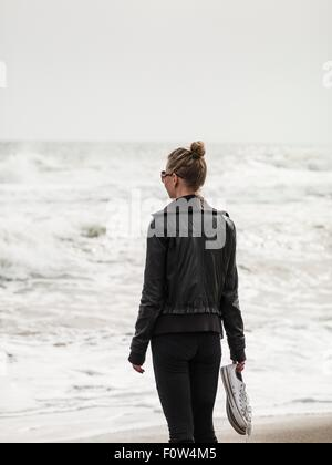 Rear view of mid adult woman looking out to sea, Torreblanca, Andalucia, Spain - Stock Photo