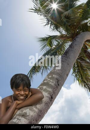 Portrait of smiling young woman leaning against palm tree - Stock Photo