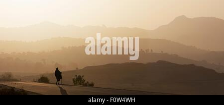 Rear view of senior man in traditional clothing looking out over landscape at sunset, Ethiopia, Africa