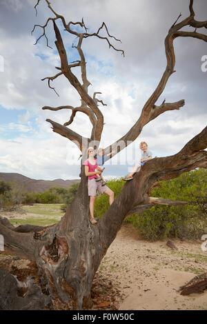 Portrait of mother and sons, standing on dead tree, Purros, Kaokoland, Namibia - Stock Photo
