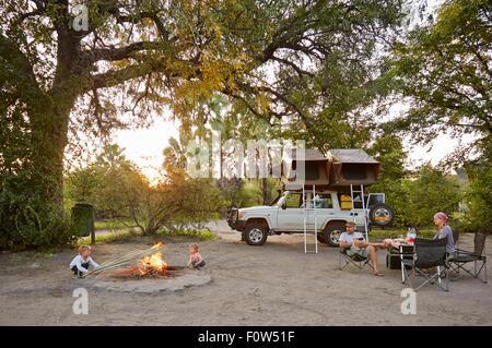 Off road vehicle parked, family relaxing around camp fire, Nata, Makgadikgadi, Botswana - Stock Photo