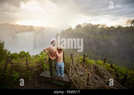 Two young boys standing on ledge admiring the view, rear view, Victoria Falls, Livingstone, Zimbabwe - Stock Photo