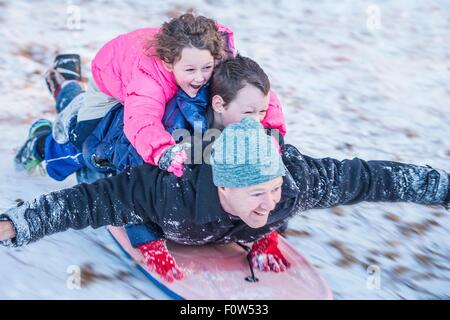 Portrait of father, son and daughter laying on top of each other riding sledge down hill - Stock Photo