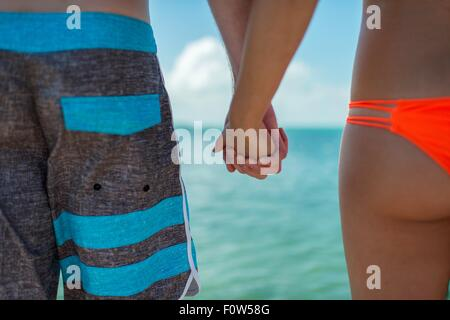 Cropped view of young couple holding hands in front of blue sea, Islamorada, Florida, USA - Stock Photo