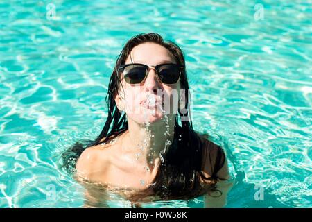 Portrait of young woman in swimming pool squirting water from mouth - Stock Photo